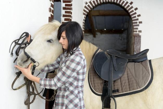 Mooi jong meisje en wit paard