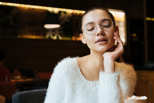 Mooi jong meisje freelancer met bril zittend in een café, denkend aan werk, sloot haar ogen