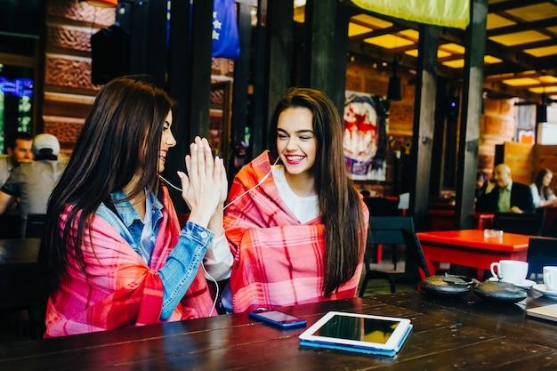 Mooi jong meisje geeft high five aan vriendin in een café aan tafel