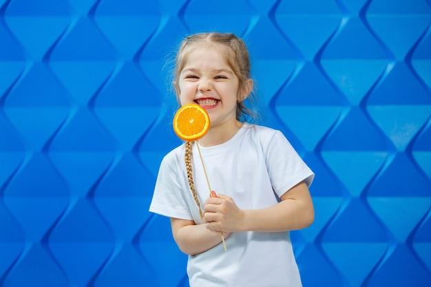 Mooi jong meisje gekleed in een wit t-shirt houdt een halve sinaasappel in haar handen en glimlacht. sinaasappelvruchten, ze bijt een sinaasappel en ze lust.