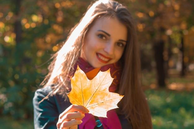 Mooi jong meisje glimlachend en met een esdoornblad in zijn hand close-up