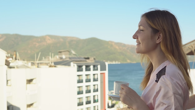 Mooi jong meisje in badjas die geurige koffie drinkt terwijl ze op het balkon van haar kamer staat