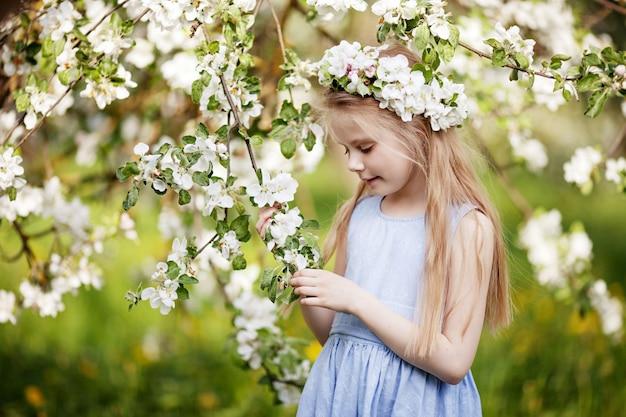 Mooi jong meisje in blauwe jurk in de tuin met bloeiende appelbomen. leuk meisje met appelboomtak