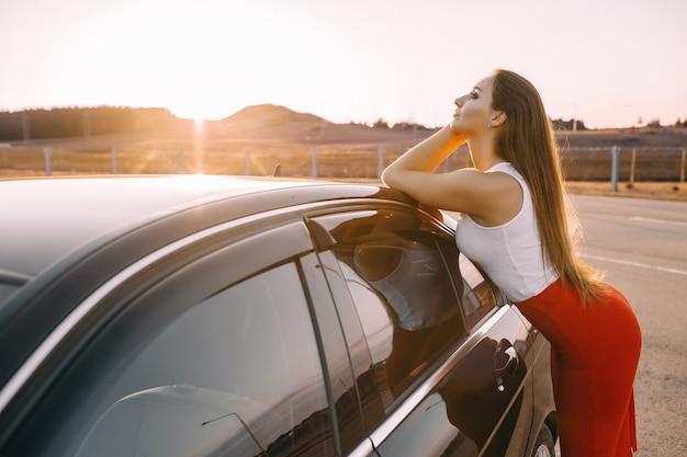 Mooi jong meisje in de buurt van een auto in de avond in de zonsondergangzon op een lege parkeerplaats