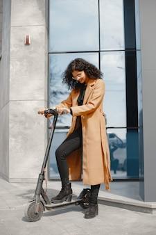 Mooi jong meisje in een bruine jas. vrouw rijdt op een elektrische scooter.