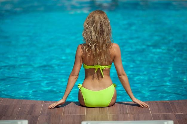 Mooi jong meisje in een gele zwembroek zonnebaden bij het zwembad in de zomer