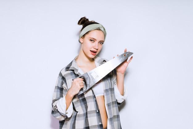 Mooi jong meisje in een geruit overhemd met een scherpe metaalzaag
