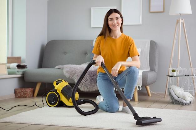 Mooi jong meisje in een goed humeur maakt het huis schoon met een stofzuiger