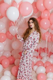 Mooi jong meisje in een jurk onder veel roze ballen.