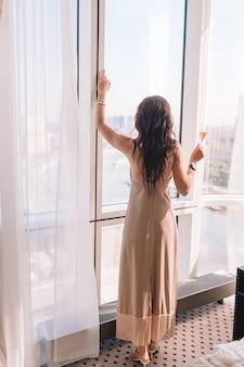 Mooi jong meisje in een lange jurk in hotelkamer