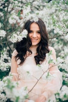 Mooi jong meisje in een lichte jurk op de achtergrond van een bloeiende tuin