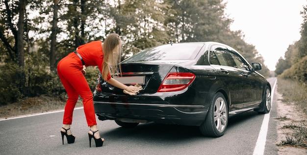 Mooi jong meisje in een rode overall reinigt een zwarte auto op een lege weg in het bos