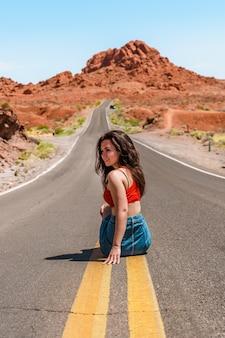 Mooi jong meisje in een spijkerrok op een schilderachtige weg in valley of fire nevada