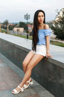 Mooi jong meisje in een stijlvolle blauwe blouse en witte korte broek op een van de stad
