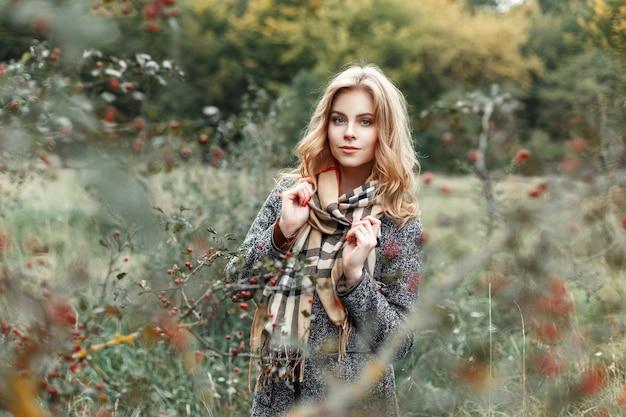 Mooi jong meisje in een vintage sjaal en jas in de buurt van de boom met bessen