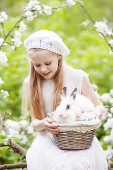 Mooi jong meisje in een witte jurk spelen met wit konijn in de lentebloesem tuin. leuke lente-activiteit voor kinderen. pasen