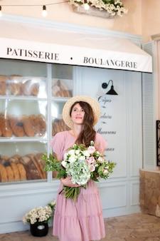 Mooi jong meisje in een zachtroze jurk met een boeket rozen in de ene hand bij de bakkerij