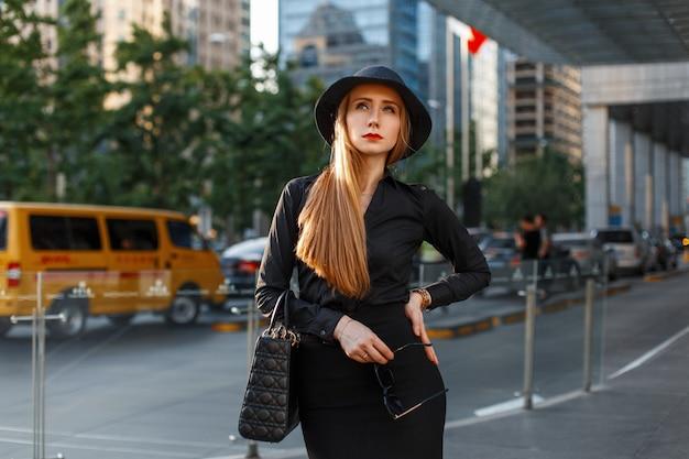 Mooi jong meisje in een zwarte hoed en stijlvolle strikte kleding