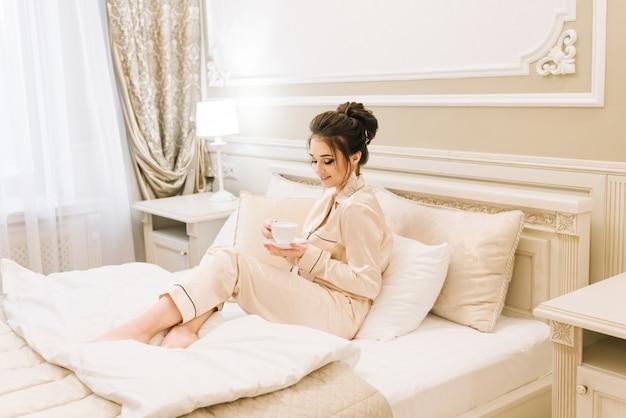 Mooi jong meisje in gouden pyjama in een luxe kamer met stijlvolle haren en make-up liggend in bed met een kopje koffie. ochtend bruid.