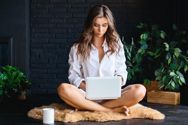 Mooi jong meisje in het overhemd van een blanke man, met behulp van laptop, zittend op het tapijt