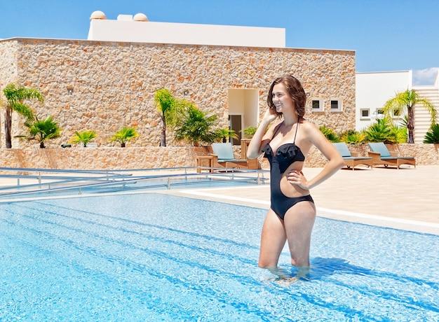 Mooi jong meisje in het zwembad in het water, glimlachend. in de zomer is het hotel.