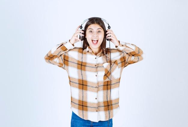 Mooi jong meisje in koptelefoon die gelukkig is en naar muziek luistert.
