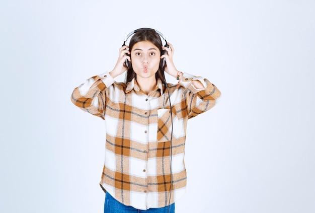 Mooi jong meisje in koptelefoon luisteren naar lied en wrang gezicht maken.