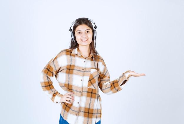 Mooi jong meisje in koptelefoon luisteren naar lied over witte muur.