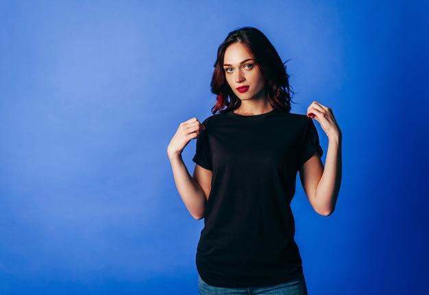Mooi jong meisje in poseren in zwart t-shirt in de studio op blauwe achtergrond