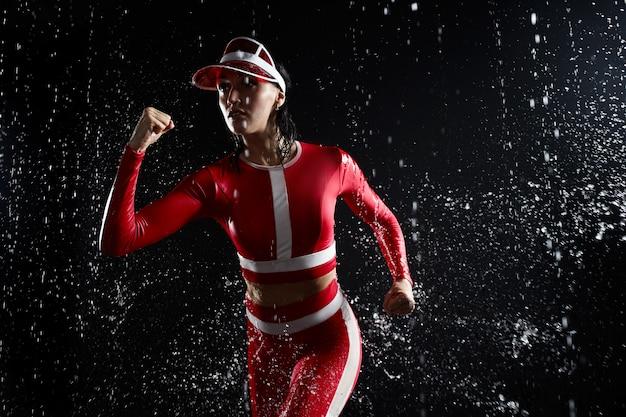 Mooi jong meisje in sportkleding die in aquastudio lopen. druppels water verspreidden zich over haar fitnesslichaam. het perfecte figuur op de achtergrond van waterspetters. slecht weer voor sport