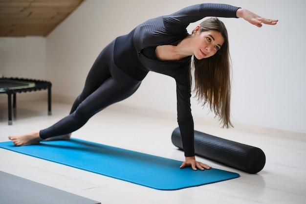 Mooi jong meisje in sportkleding houdt zich bezig met fitness op een gymnastiektapijt