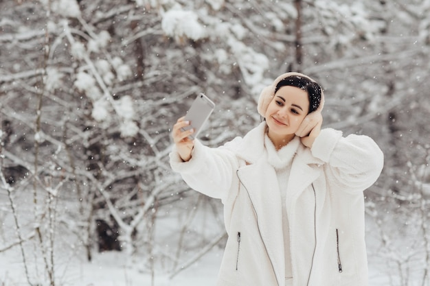 Mooi jong meisje in witte kleren en pluizige koptelefoon selfie met smartphone buitenshuis op besneeuwde winterdag.