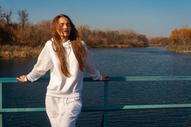 Mooi jong meisje in witte kleren staat op de brug