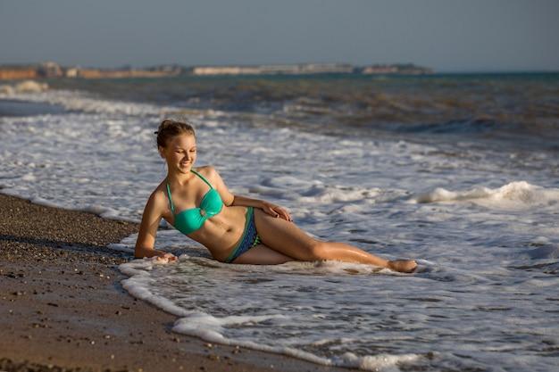 Mooi jong meisje in zwempak het stellen op het strand door het overzees op een zonnige hete dag.