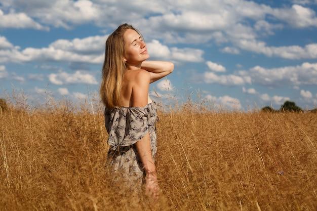 Mooi jong meisje is op tarweveld in zonnige dag. een verleidelijk meisje met lang licht haar wandeling in het tarweveld gelukkig meisje in veld met aartjes landschap. weekend buiten in de zomer.