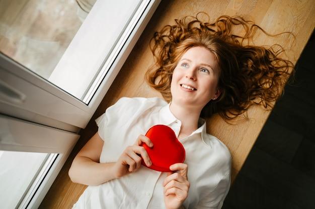 Mooi jong meisje liggend bij het raam met een cadeau voor valentijnsdag
