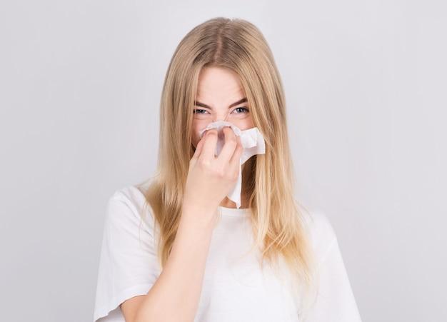 Mooi jong meisje lijdt aan een verkoudheid en snuit zijn neus in een servet. het concept van medicijnen en seizoensgebonden verkoudheden.