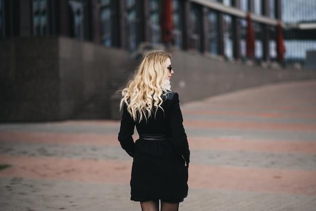 Mooi jong meisje met blond golvend haar in een zwarte jas tegen de achtergrond van moderne gebouwen