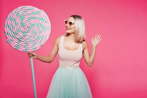 Mooi jong meisje met blond haar dat een top en een rok draagt die zich met enorme zoete lolly's op roze bevindt