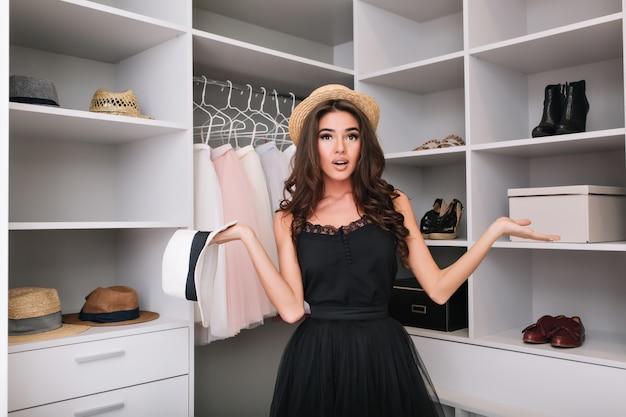 Mooi jong meisje met bruin lang krullend haar in strohoed die probeert te kiezen wat te dragen. grote luxe kledingkast. model heeft een modieuze uitstraling en draagt een zwarte elegante jurk.