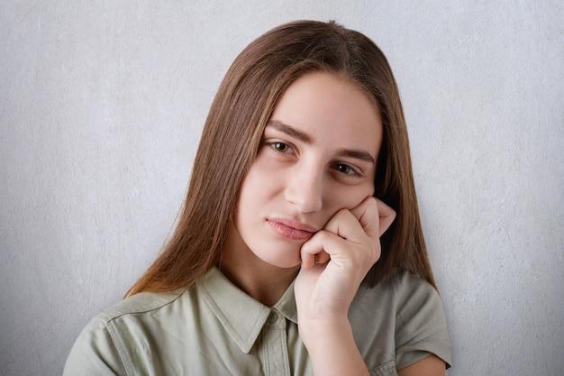 Mooi jong meisje met bruine ogen met volle lippen en lang recht bruin haar met een droevige blik en haar hand op haar wang houdend.