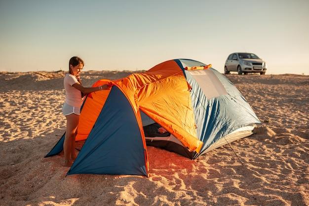 Mooi jong meisje met donker haar zet een tent op het strand. auto kamperen op een verlaten zandstrand