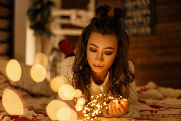 Mooi jong meisje met een glimlach in een gebreide trui met vakantielichten op het bed
