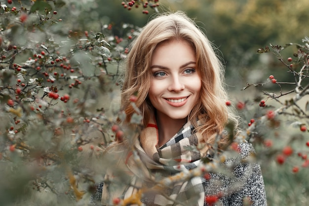 Mooi jong meisje met een glimlach in een warme sjaal in de buurt van een boom met bessen