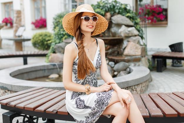 Mooi jong meisje met een glimlach in zonnebril en hoed zittend op een bankje in het park.