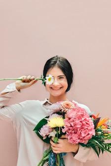Mooi jong meisje met een groot roze boeket