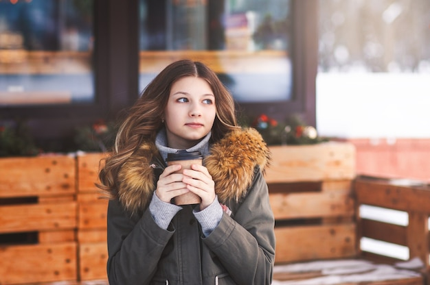 Mooi jong meisje met een kopje koffie op het terras van het café