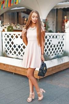 Mooi jong meisje met een lieve glimlach in een roze jurk met handtas wandelen in de stad