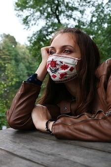 Mooi jong meisje met een masker met een geborduurd patroon zit aan een houten tafel buiten in een bos, tuin of park