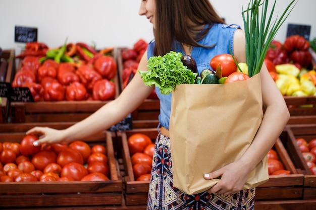 Mooi jong meisje met een papieren zak met winkelen in een groente winkel